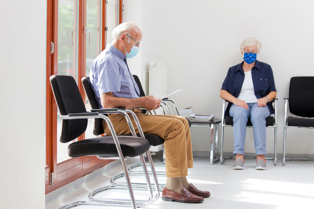 man and woman waiting at doctor's office in masks