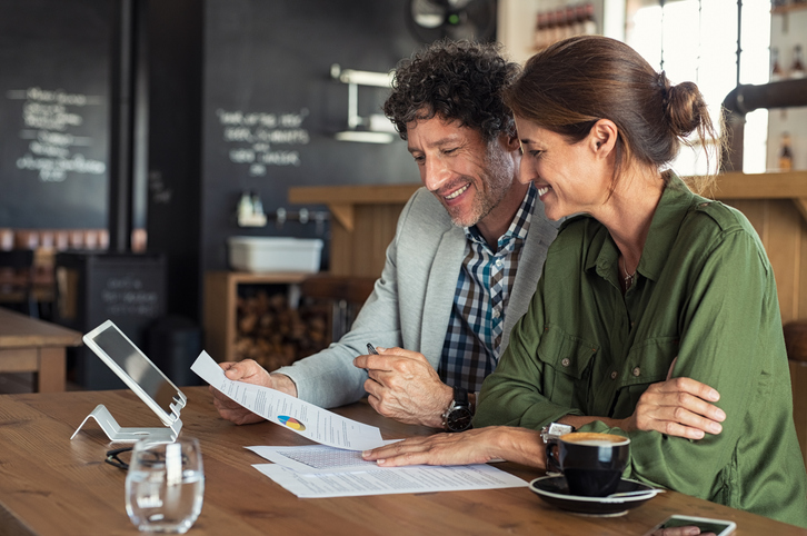 Man and woman reviewing paperwork at a cafe