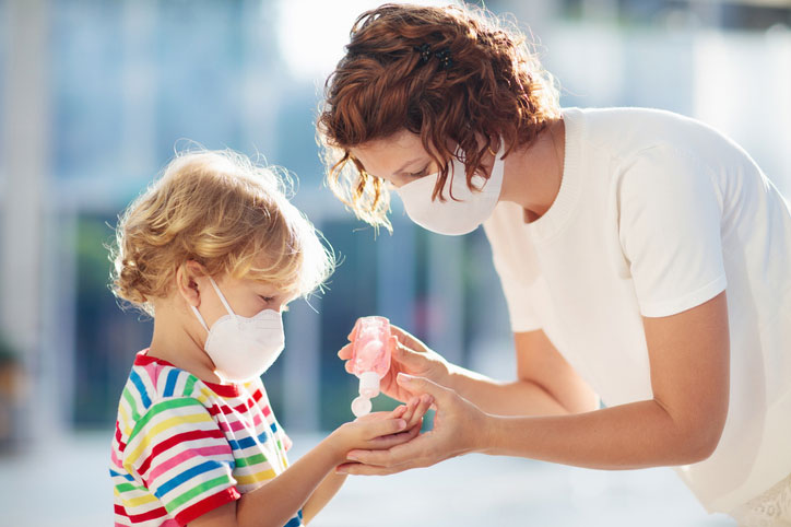 woman helps kid with hand sanitzier and mask