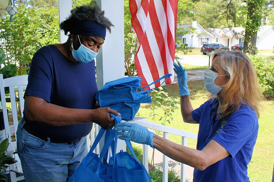 BlueCross employee hands meals to elderly woman on front porch