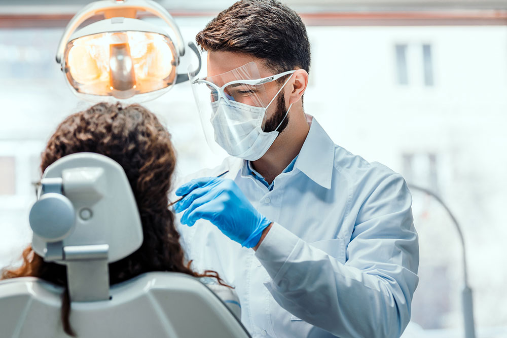 Dentist works on patient with mask and face shield